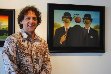 Geoffrey Gersten with one of his paintings on view at Modified Arts.