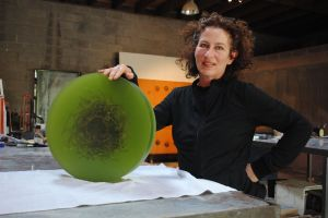 Mayme Kratz in her studio holding a small resin piece in its final stages.