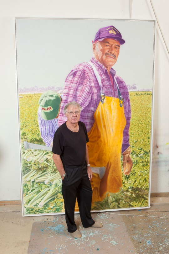 """Don Coen with his 9-foot-high acrylic on canvas """"Angel"""" from """"The Migrant Series"""" at the Phoenix Art Museum. Image courtesy of the artist."""