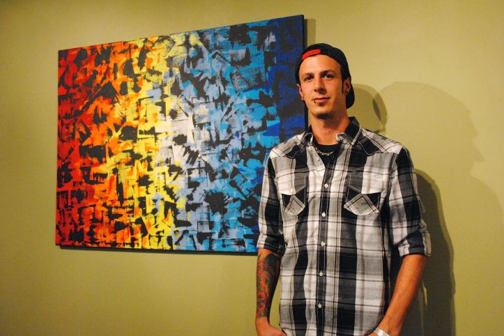 Luke Kaminski forgoes the paintbrush to use a credit card dipped in paint to create his abstract works. His paintings are up at the new Skyline Lofts Art Gallery.