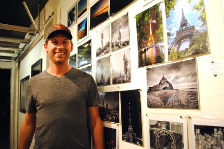 Andrew Pielage runs Drive-Thru Gallery, and here he's in front of several examples of his captivating photography from around the world.